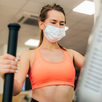 얼굴 마스크와 함께 운동하는 체육관에서 여자