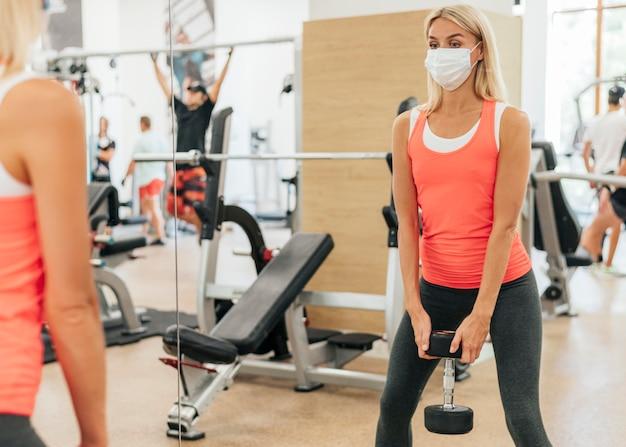 마스크와 체육관 훈련에서 여자