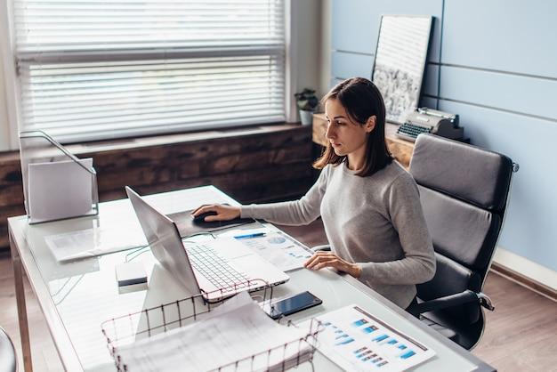 Женщина за офисным столом работает с ноутбуком, смотрит на экран.