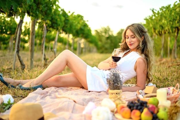 グラスワインとピクニックの女性。ブドウ園の緑の背景
