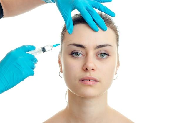 Женщина у пластического хирурга изолирована на белой стене