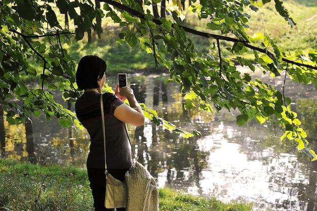 池の女性が携帯電話で風景の写真を撮る