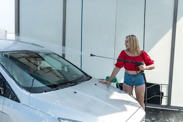 셀프 서비스 세차장에 있는 여성이 고압 호스로 차에서 거품을 씻어내고 있습니다.