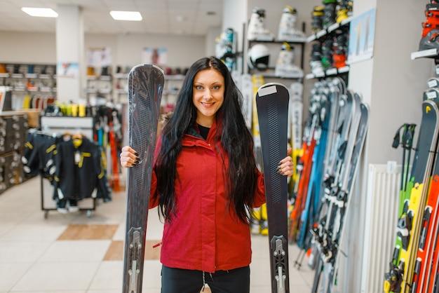 下り坂のスキーを手に持ったショーケースの女性、正面図、スポーツショップでのショッピング。