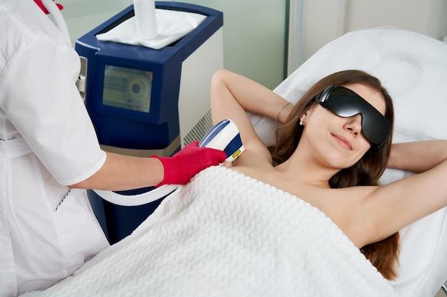 Женщина в спа-салоне, получающая лазерную эпиляцию на подмышке