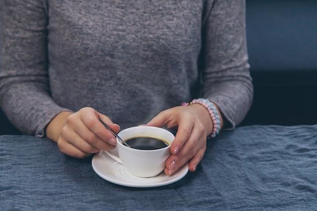 Женщина за столом с чашкой кофе