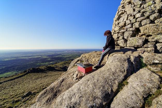 Женщина на вершине горы, созерцая виды после достижения вершины. мадрид.