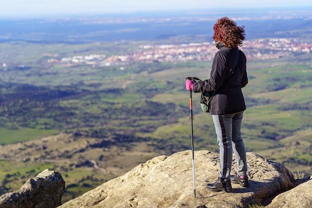 Женщина на вершине горы, созерцая виды после достижения вершины.