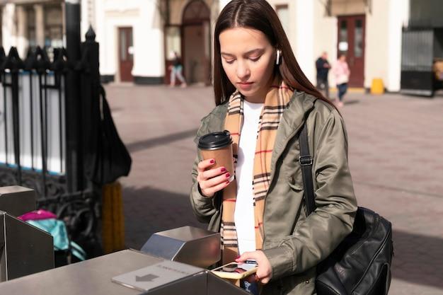 Женщина у турникетов держит кофе