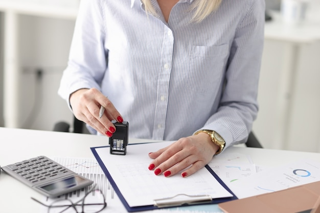 Женщина за рабочим столом ставит печать на документы. концепция развития стратегии деловых соглашений