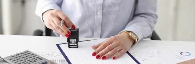 Женщина за рабочим столом ставит печать на документы концепции развития стратегии деловых соглашений