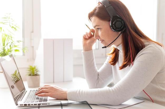 ノートパソコンでビデオ通話をしている職場の女性