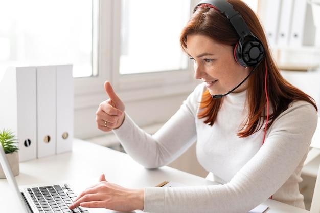 노트북에 화상 통화를 갖는 직장에서 여자