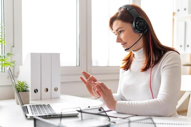Женщина на работе с видеозвонком на ноутбуке
