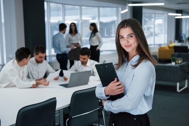 職場の女性。バックグラウンドで従業員とオフィスに立っている若い女の子の肖像画
