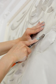 끌 도구로 직장에서 여성이 벽에 지어져 패턴을 새깁니다.