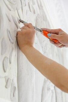 彫刻刀を使って仕事をしている女性が壁に浅浮き彫りの模様を彫る