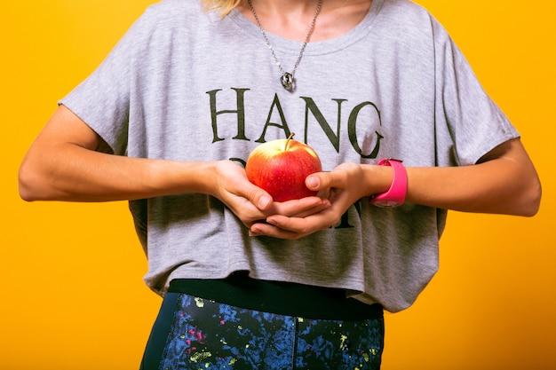 アップルを保持しているあなたのカジュアルな服装の女性