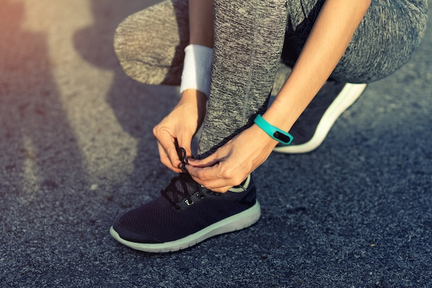 Woman athlete is sitting tying running shoes before to run.
