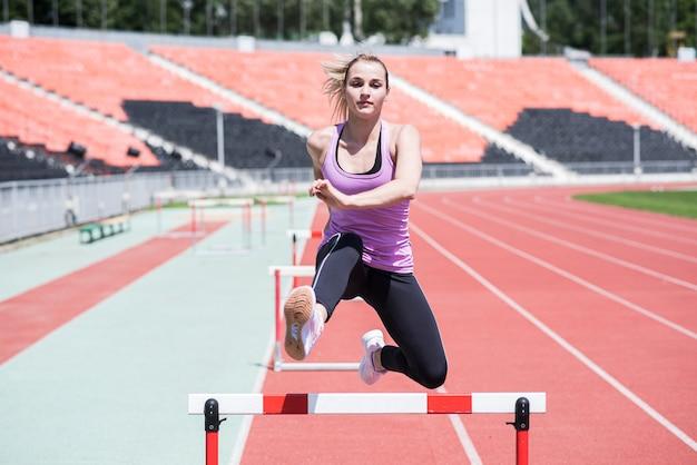 Спортсмен женщина прыгает через препятствие. бег с препятствиями. активный образ жизни