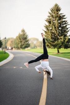 야외에서 운동을 하 고, 도로에 재주 넘기를 뛰어 드는 여자 선수.