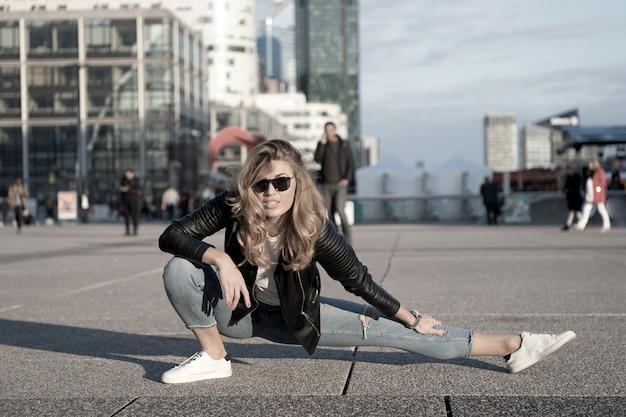 Спортсменка или танцовщица разделили ногу в париже, франция. чувственная женщина с длинными волосами в темных очках и джинсах, мода. йога, пилатес, танцы, спорт. мода, красота, взгляд. отпуск, путешествия, страсть к путешествиям.