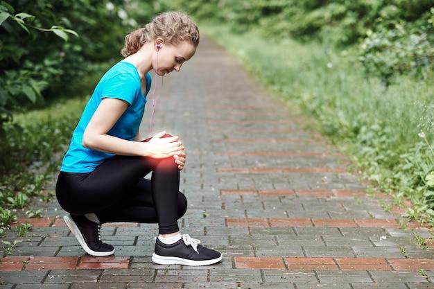 痛みで膝に触れる女性アスリートランナー、夏の公園で走っているフィットネス女性。健康的なライフスタイルとスポーツのコンセプト。
