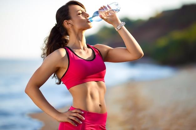 Женщина спортсменка делает перерыв, она пьет воду, выходит на пробежку в жаркий день. женщина работает на пляже на закате