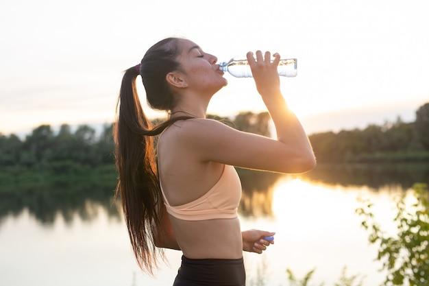 Спортсменка делает перерыв, она пьет воду, на пробежке в жаркий день