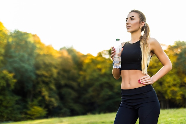 여자 운동 선수는 더운 날에 물을 마시고 휴식을 취합니다.