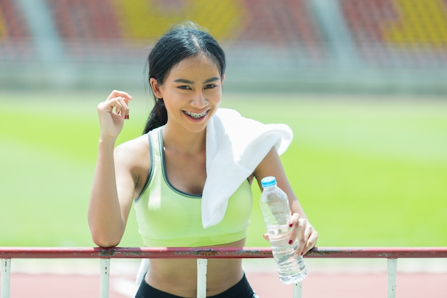 Woman athlete takes a break and drinks water