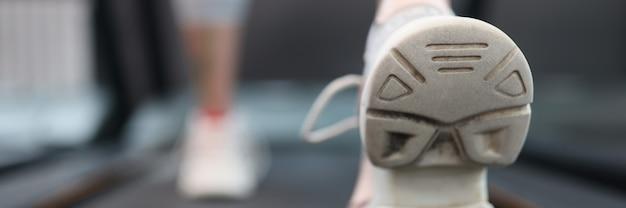 ジムのクローズアップ有酸素運動の概念でトレッドミル上を歩く女性アスリート