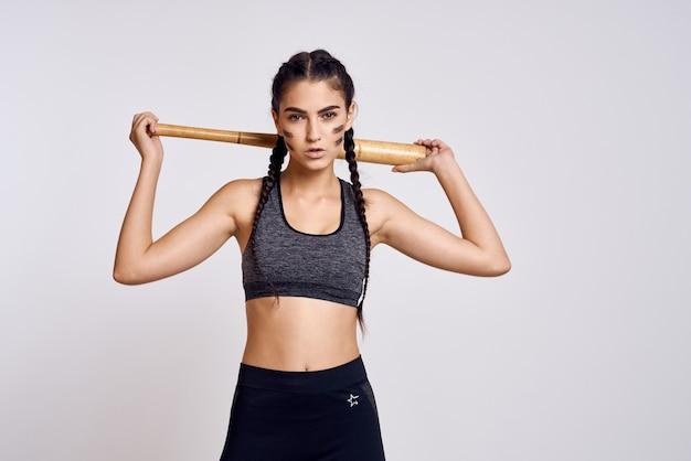 Тренируется женщина-спортсмен с битой в руках