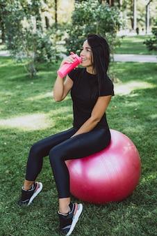 Спортсменка с большим фитнес-мячом пьет протеин из шейкера после тренировки