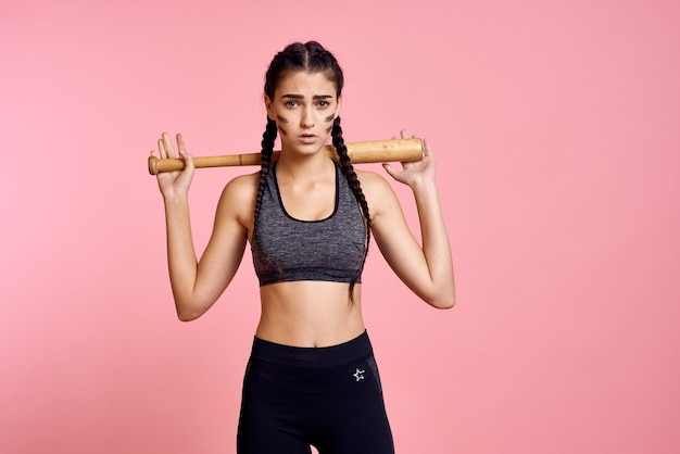 Woman athlete with a bat in her hands is training in the studio
