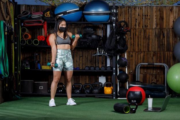 새로운 표준을 위한 마스크를 쓴 컴퓨터로 온라인 교육을 하는 여성 운동선수