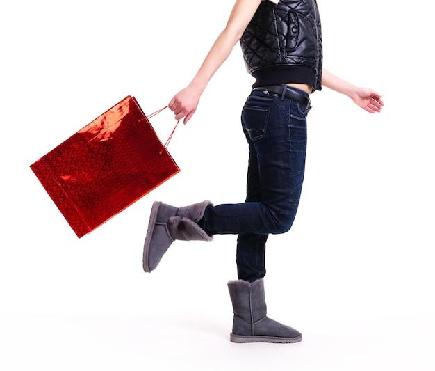 Donna in stivali di autunno e blue jeans con la condizione rossa del sacchetto della spesa - isolata su bianco.