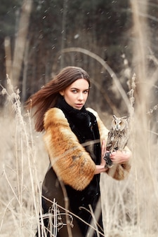 Woman autumn in coat with owl on hand first snow
