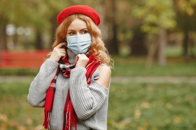 Donna nella foresta di autunno. persona in maschera. tema coronavirus. signora in una sciarpa rossa.