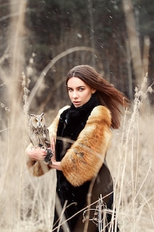 Woman in autumn in fur coat with owl on hand first snow. beautiful brunette girl with long hair in nature, holding an owl. romantic, delicate look girls