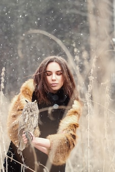 Woman in autumn in fur coat with owl on hand