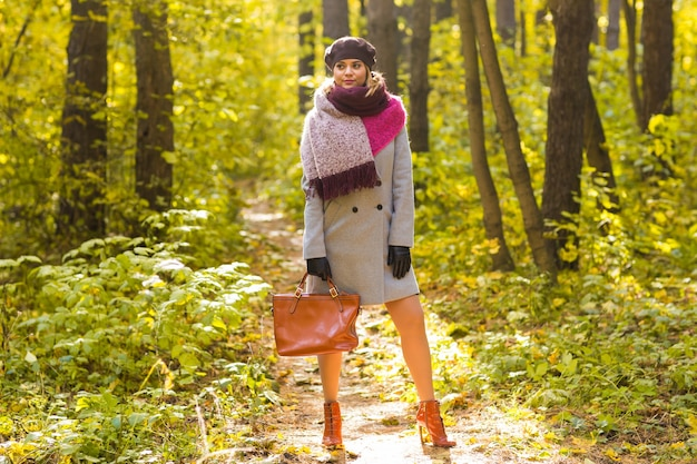 Woman in autumn park posing with bag