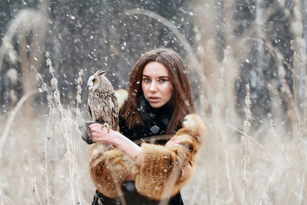 Woman in autumn with owl on hand first snow