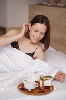 Donna sveglia sul letto con presente e caffè con marshmallow in piedi vicino a lei. mornig sorpresa
