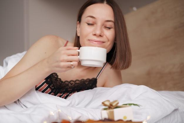 Donna sveglia sul letto con presente e caffè con marshmallow in piedi vicino a lei.