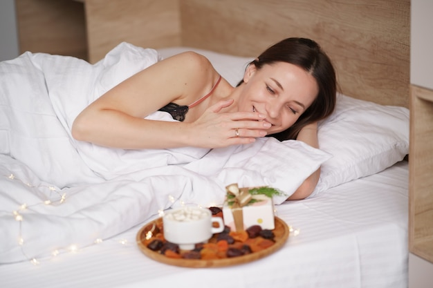 女性は彼女の近くに立っているマシュマロとプレゼントとコーヒーでベッドで目を覚まします。
