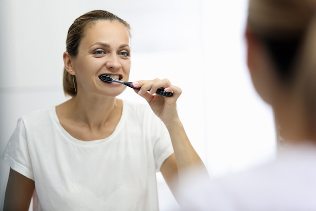 Woman in awhite t-shirt is brushing her teeth in front of mirror
