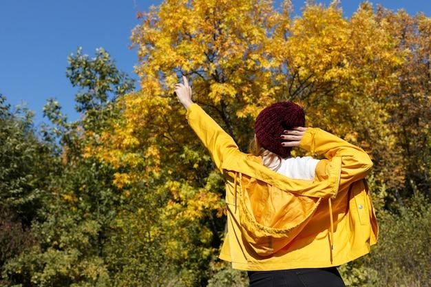 紅葉と青い空の前に黄色い秋のレインコートに戻った女性。明るい秋