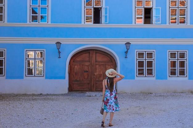 여자는 다시 목조 아치형 문이있는 파란색 중세 아늑한 집 앞에 서 있습니다.
