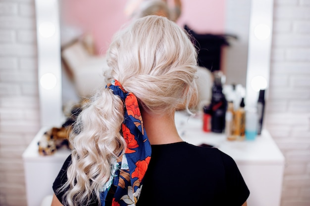 Woman back with blonde curly hair style